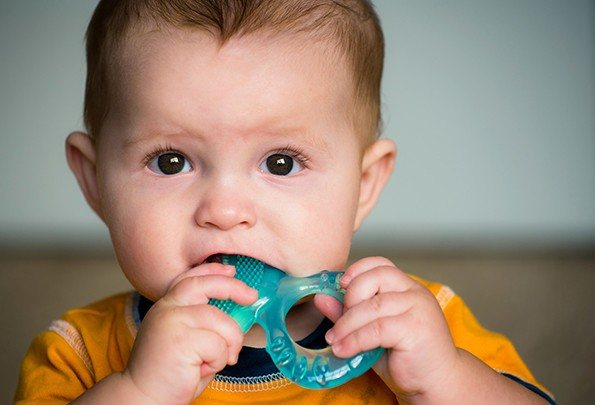 Baby chewing on teeth ring
