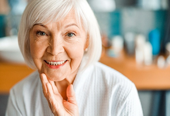 Older woman gently touching chin; smiling with dentures in Everett, WA
