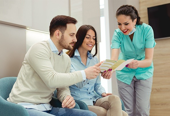 Man and woman looking at brochure with dental team member