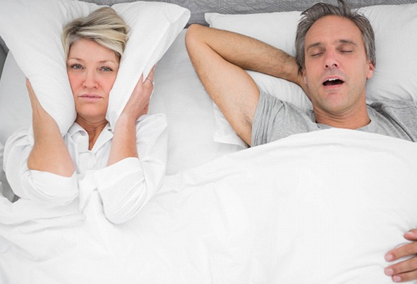 Woman covering ears while man snores due to sleep apnea in Everett, MA