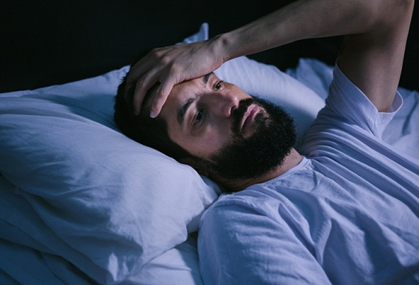 Man with sleep apnea lying awake at night